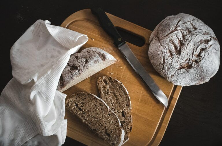 nóż i pokrojony bochenek chleba na desce